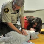 Sheriff Officer assists Genete in CPR demo. Sheriff's & Search & Rescue Units need this life-saving training for the K9s under their care.